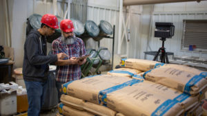 two men in red hard hats look at a tablet while standing in a feed mill